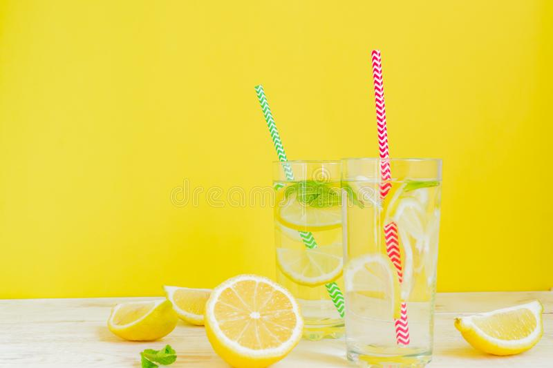 Two glasses of homemade lemonade with lemons, mint and  paper straw on yellow background. Summer refreshing beverage royalty free stock images