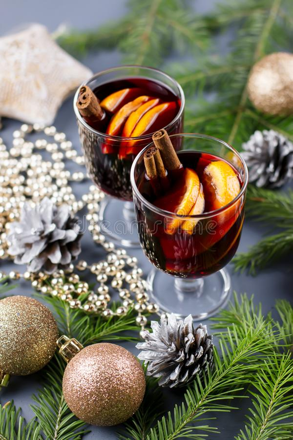 Two glasses of hot mulled wine with spices and sliced orange. Christmas drink with candle and decorations. Top view royalty free stock photo