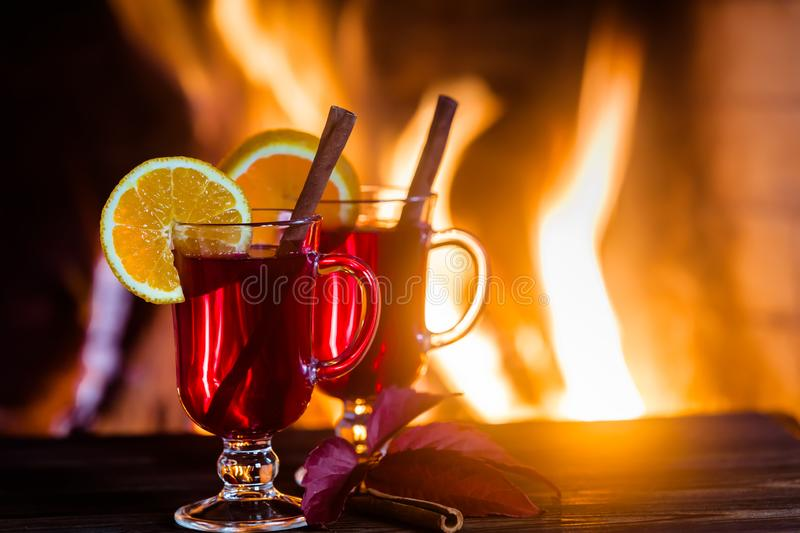Two glasses of hot mulled wine with spices on wooden table against fireplace. royalty free stock images