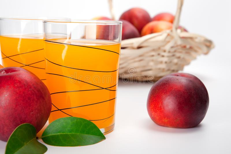 Two glasses of juice and fresh peaches royalty free stock photos