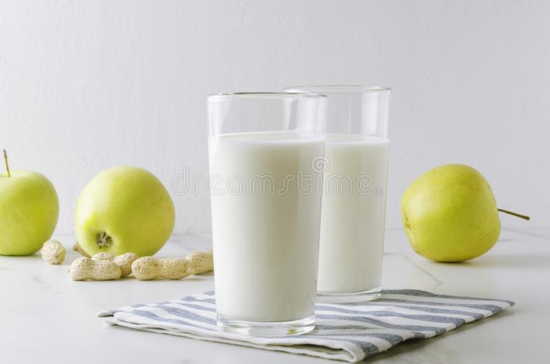 Two glasses of kefir,aplles,nuts,napkin on white table against white background in the kitchen.Concept of milky diet and healthy f royalty free stock photography