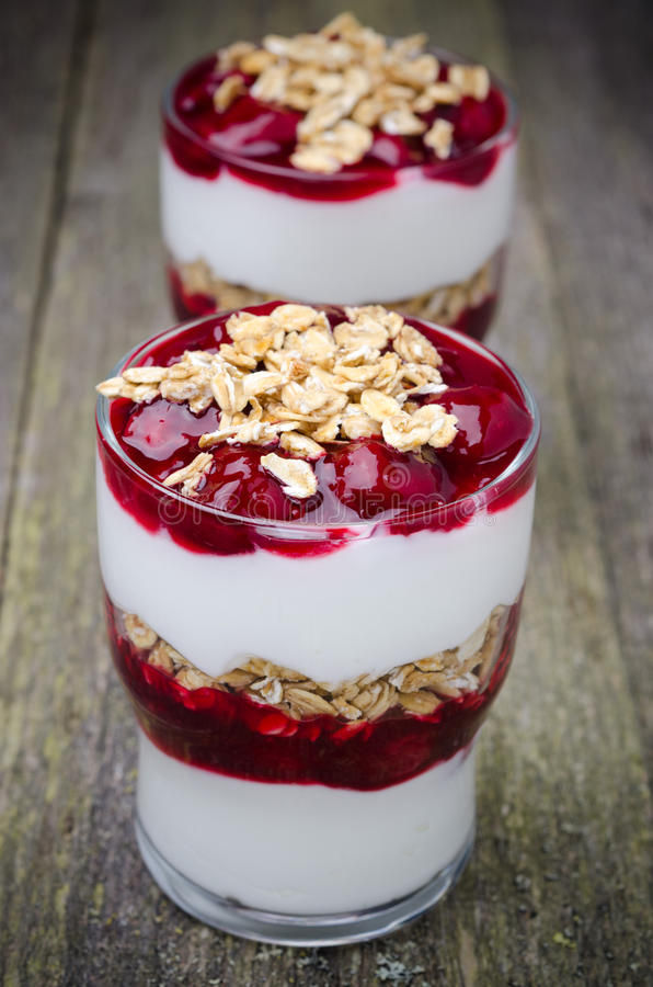 Two glasses with layered dessert with yogurt, cherry, granola. Two glasses with layered dessert with yogurt, cherries and granola, vertical stock images