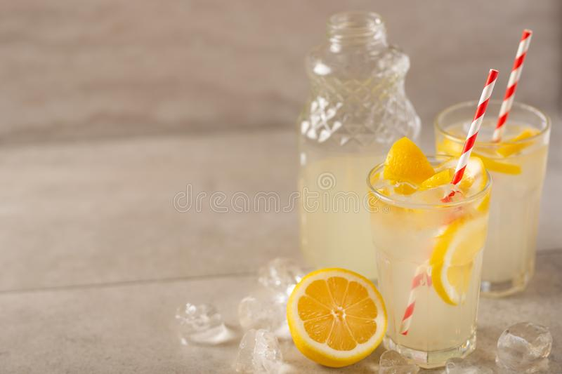 Two glasses of lemonade with lemons and lime and straw, a bottle with a cool drink and summer mood, with ice, freshness in hot. Summer royalty free stock photography