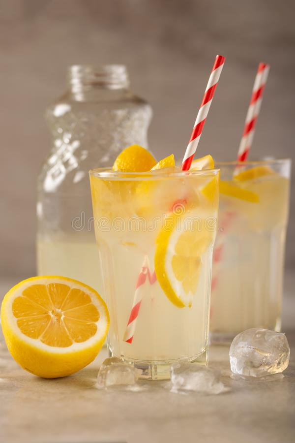 Two glasses of lemonade with lemons and lime and straw, a bottle with a cool drink and summer mood, with ice, freshness in hot stock photo
