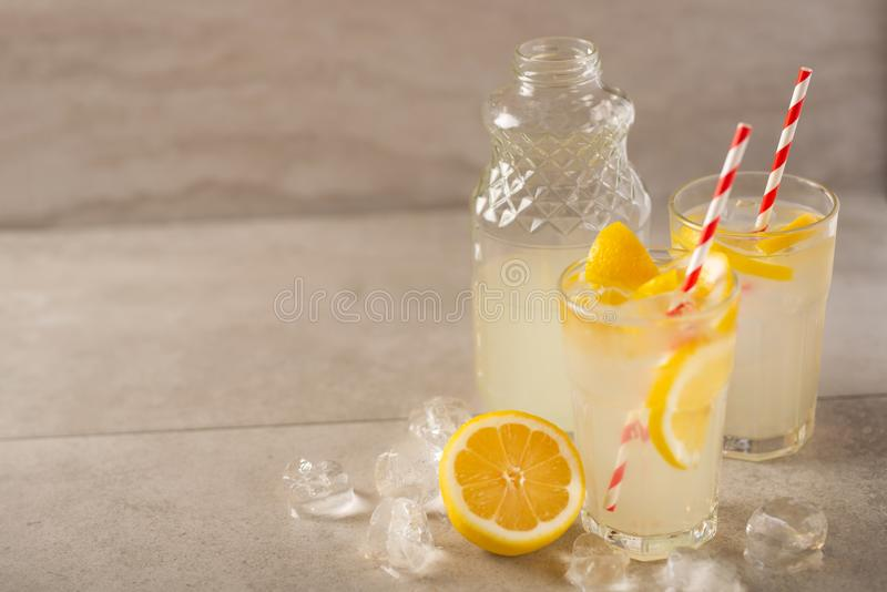 Two glasses of lemonade with lemons and lime and straw, a bottle with a cool drink and summer mood, with ice, freshness in hot. Summer stock photography