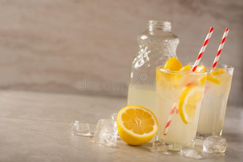 Two glasses of lemonade with lemons and lime and straw, a bottle with a cool drink and summer mood, with ice, freshness in hot. Summer stock image