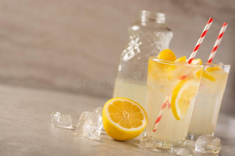 Two glasses of lemonade with lemons and lime and straw, a bottle with a cool drink and summer mood, with ice, freshness in hot. Summer royalty free stock photo