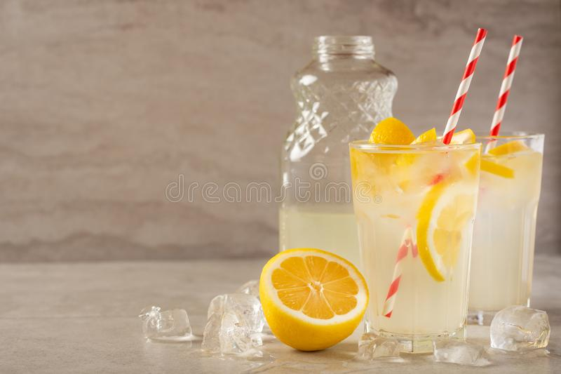 Two glasses of lemonade with lemons and lime and straw, a bottle with a cool drink and summer mood, with ice, freshness in hot. Summer royalty free stock image