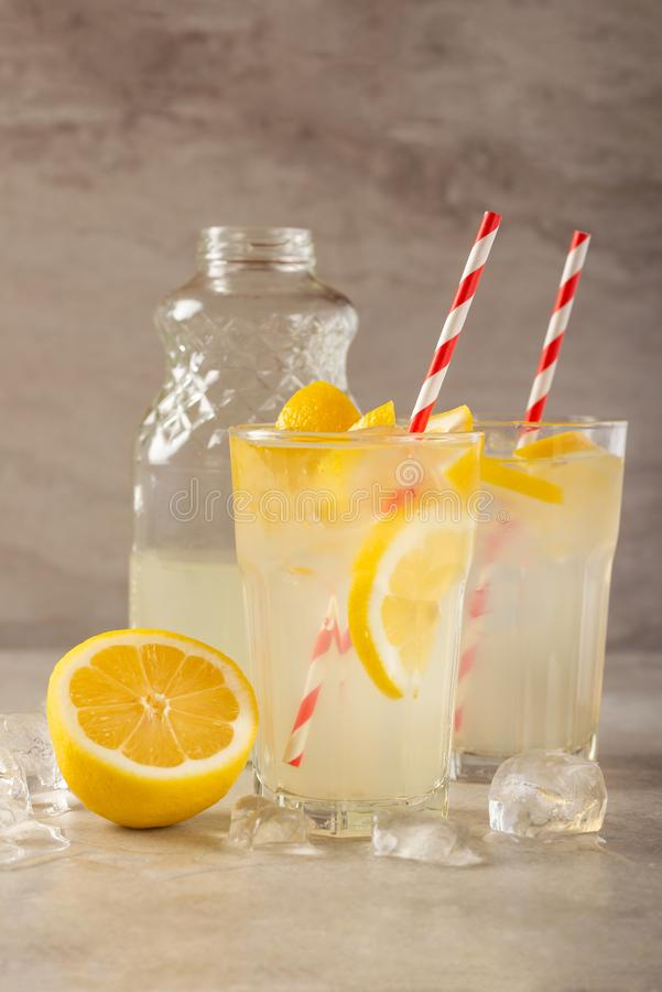 Two glasses of lemonade with lemons and lime and straw, a bottle with a cool drink and summer mood, with ice, freshness in hot royalty free stock photo