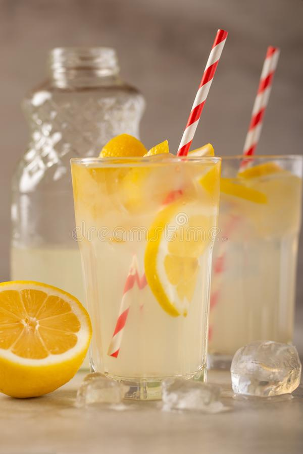 Two glasses of lemonade with lemons and lime and straw, a cool drink and summer mood, with ice.  stock photography