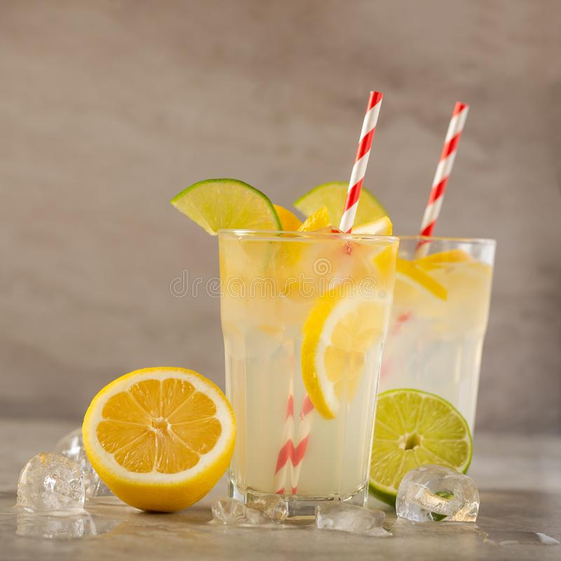 Two glasses of lemonade with lemons and lime and straw, a cool drink and summer mood, with ice royalty free stock images