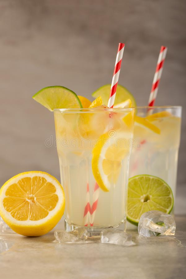 Two glasses of lemonade with lemons and lime and straw, a cool drink and summer mood, with ice royalty free stock photo