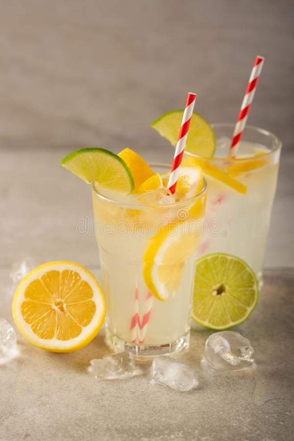 Two glasses of lemonade with lemons and lime and straw, a cool drink and summer mood, with ice stock photos