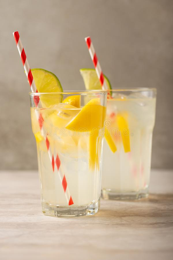 Two glasses of lemonade with lemons and lime and straw, a cool drink and summer mood, with ice royalty free stock photography