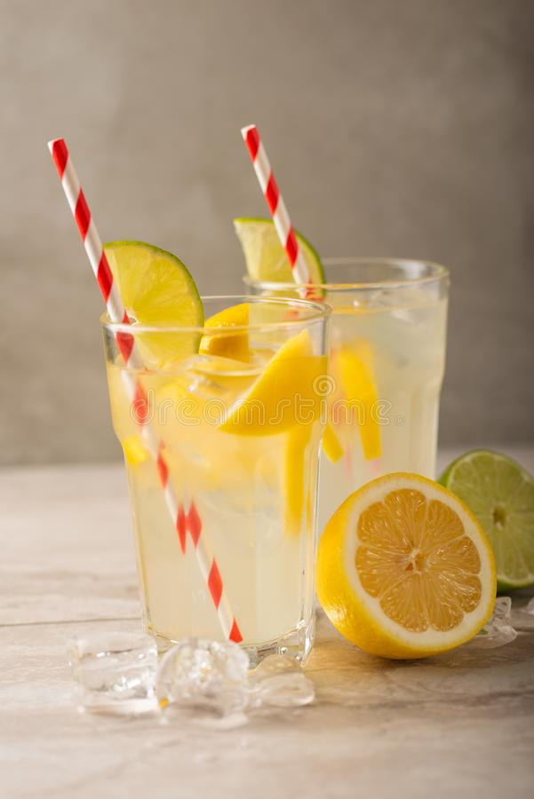 Two glasses of lemonade with lemons and lime and straw, a cool drink and summer mood, with ice.  royalty free stock images
