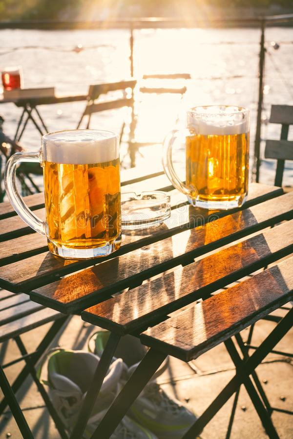 Two glasses of light beer with foam on a wooden table.On a boat. Garden party. Natural background. Alcohol. Draft beer. Landscape,. Golden royalty free stock images