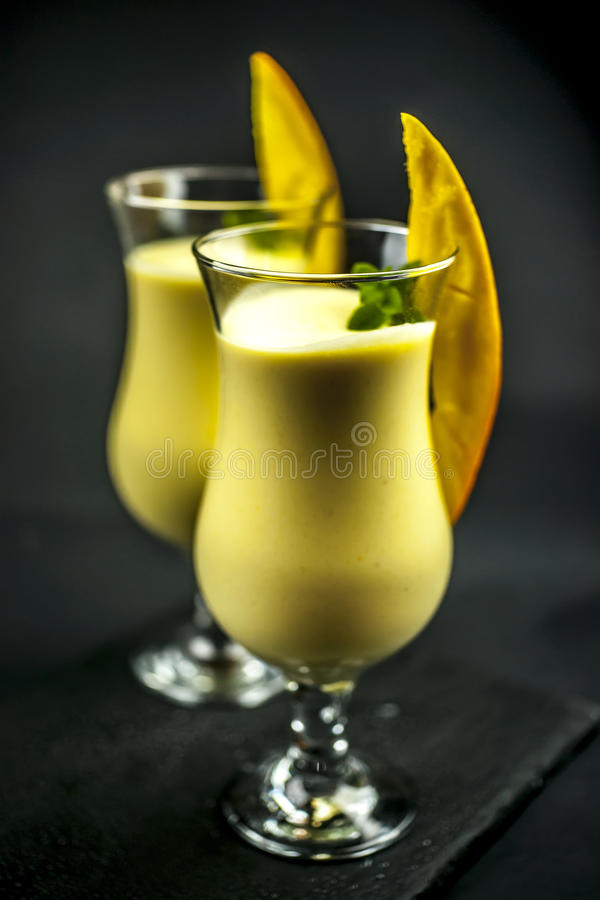 Two glasses of mango lassi stock images