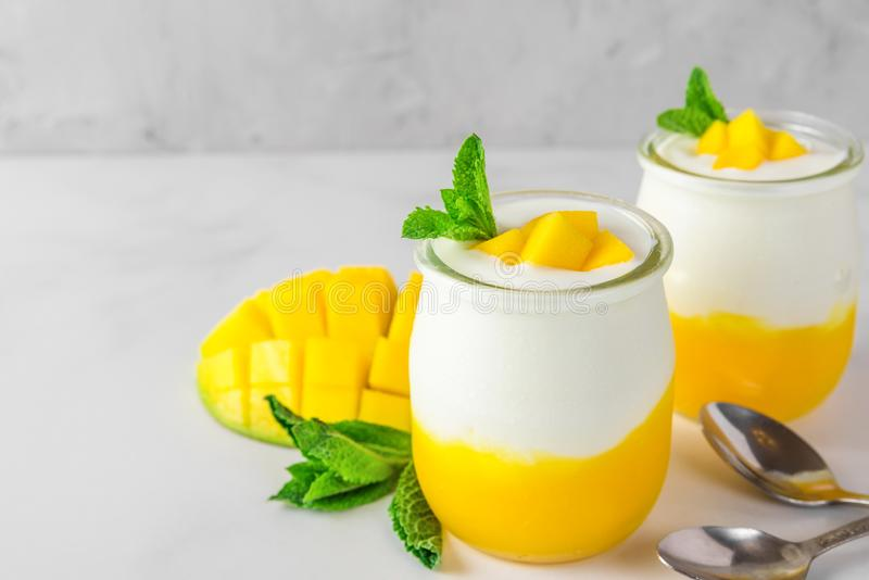 Two glasses of mango yogurt with fresh fruits and mint over white concrete background. healthy breakfast. Close up stock photography