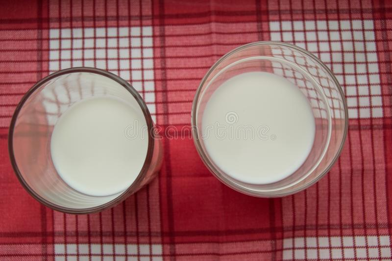 Two glasses of milk stand on a red checkered cloth, top view royalty free stock image