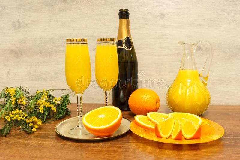 Two glasses of mimosa cocktail, a bottle of champagne, a decanter with orange juice, fresh oranges, mimosa sprig on a wooden table royalty free stock photo
