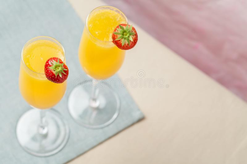 Mimosa cocktail and strawberries. Two glasses of mimosa cocktail champagne with orange juice and fresh strawberries royalty free stock photography