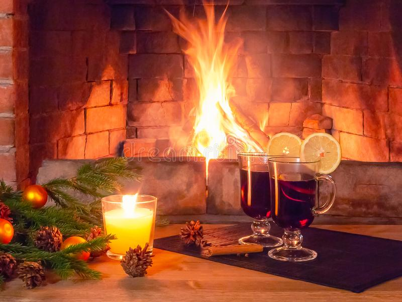 Two glasses with mulled wine, a candle, fir branches with decorations on a wooden table against the background of a stock image