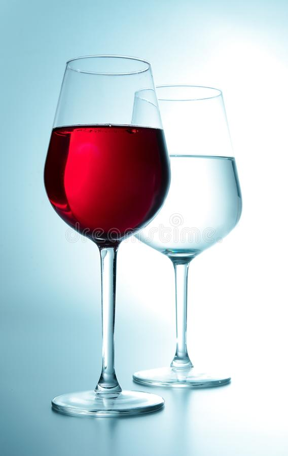 Two glasses. One with wine and the other with water. White turquoise tone. Close-up. stock photography