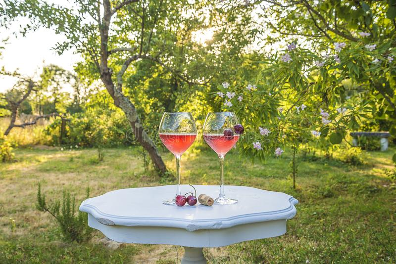 Two glasses of pink wine and cherries on the beautiful white table in the blooming garden. On sunny day stock photo