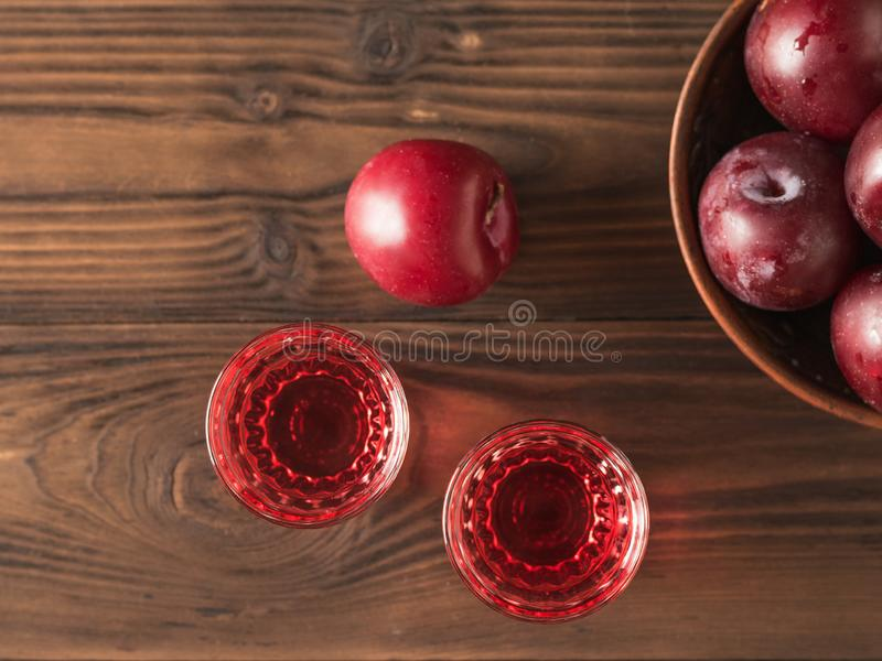 Two glasses of plum alcohol and a bowl of plums on a wooden table. Flat lay. Two glasses of plum alcohol and a bowl of plums on a wooden table. Homemade stock photo