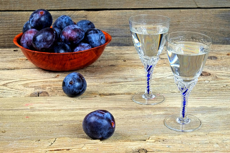 Two glasses of plum brandy with plums stock image