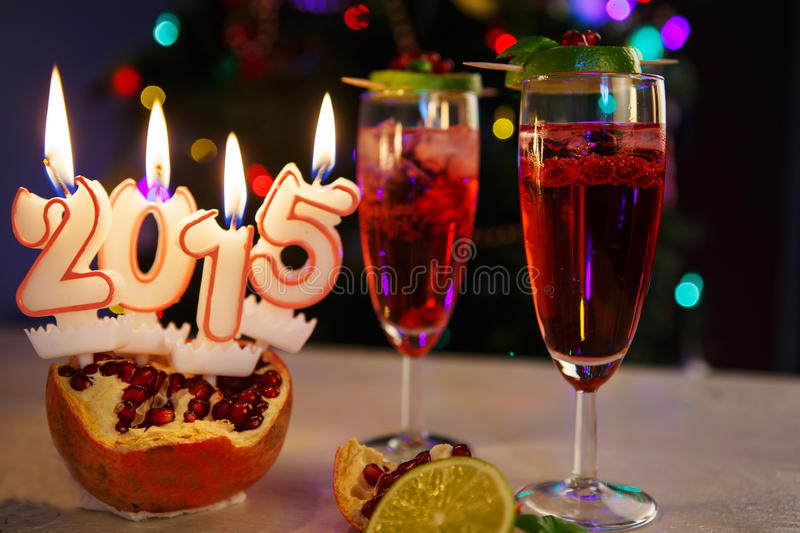 Two glasses with red champagne and candles 2015. Two glasses with red pomgranate champagne and burning candles 2015 with christmas tree on background royalty free stock image