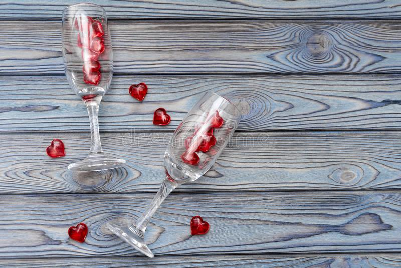 Two glasses, red figures in the shape of a heart on a wooden background. romantic date. stock photography