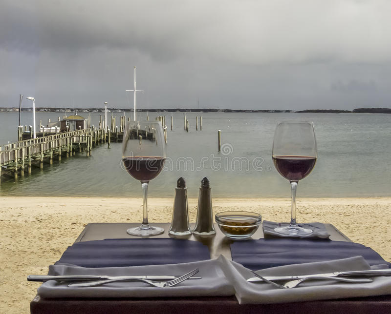 Two glasses of red wine on a beach side restaurant. A cloudy afternoon is a good time to have lunch at a beach side restaurant with a glass of Cabernet royalty free stock photos