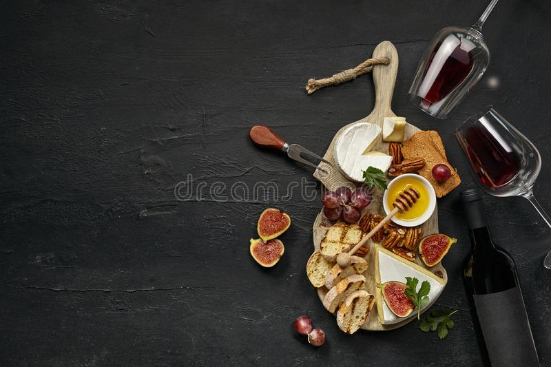 Two glasses of red wine and cheese plate with fruit on the black stone stock photos