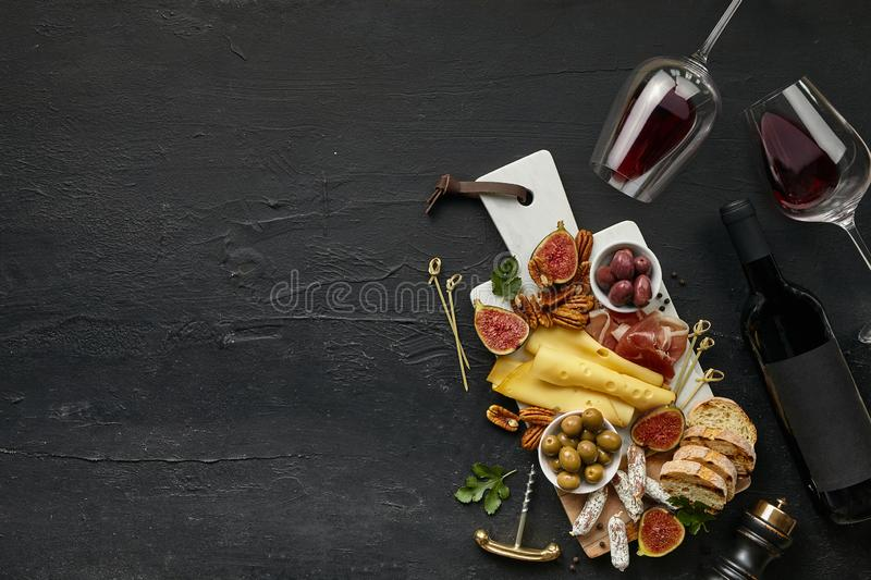 Two glasses of red wine and cheese plate with fruit on the black stone stock photo