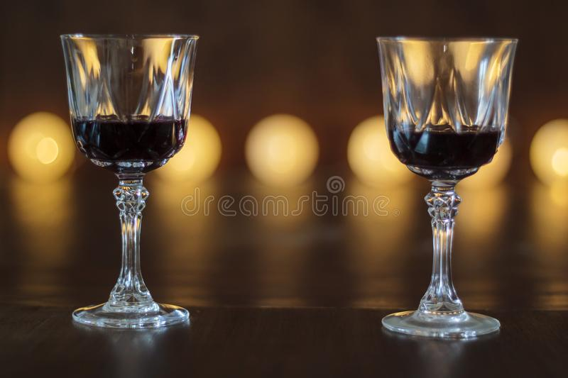 Two glasses of red wine with defocused lights on the background. Two crystal glasses of red wine with defocused lights on the background stock image