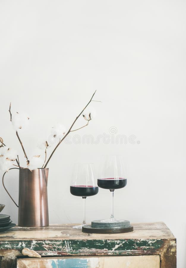Two glasses of red wine over rustic kitchen countertop stock image