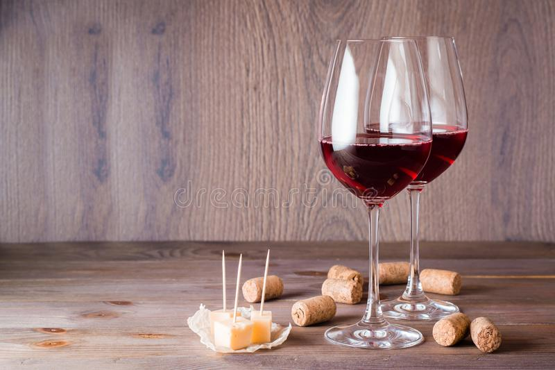 Two glasses with red wine, pieces of cheese and cork on a wooden table royalty free stock image