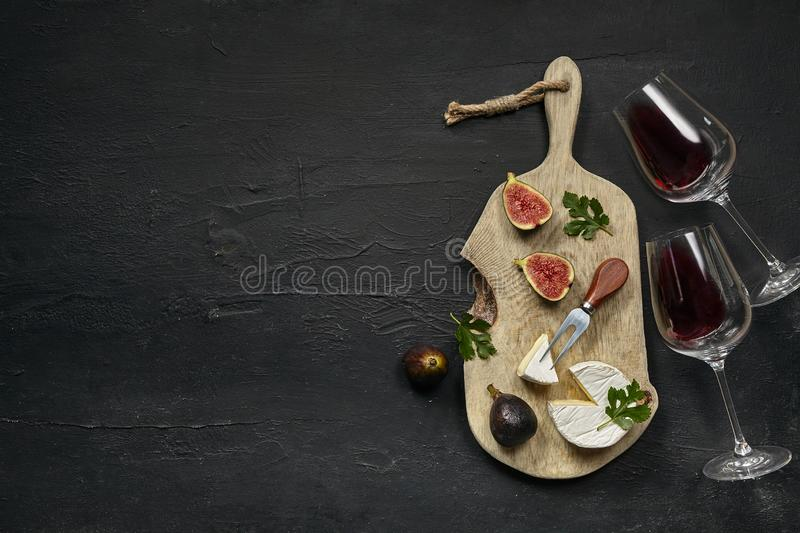 Two glasses of red wine and a tasty cheese plate on a wooden kitchen plate. royalty free stock image