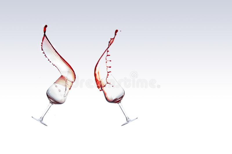 Two glasses of red wine with the wine splashing out of a glass, isolated over white background royalty free stock photography