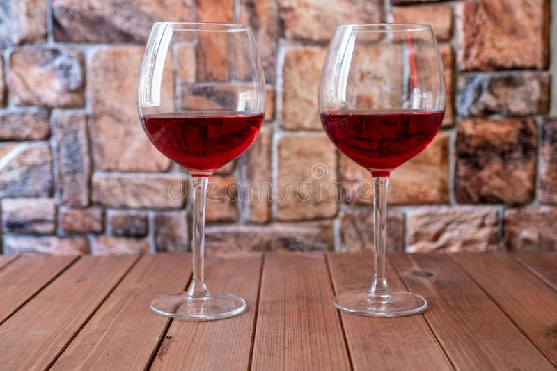 Two glasses of red wine on a wooden table stock image