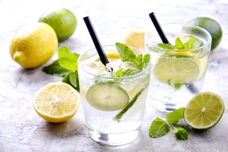 Two glasses of refreshing non alcoholic mojito lemonade drink with organic lemon, lime slices, mint leaves, straw, ice cubes on gr royalty free stock photos