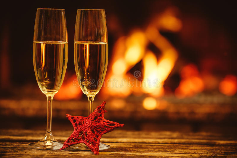 Two glasses of sparkling champagne in front of warm fireplace. C. Ozy relaxed magical atmosphere in a chalet. Holiday concept. Beautiful background with stock photography