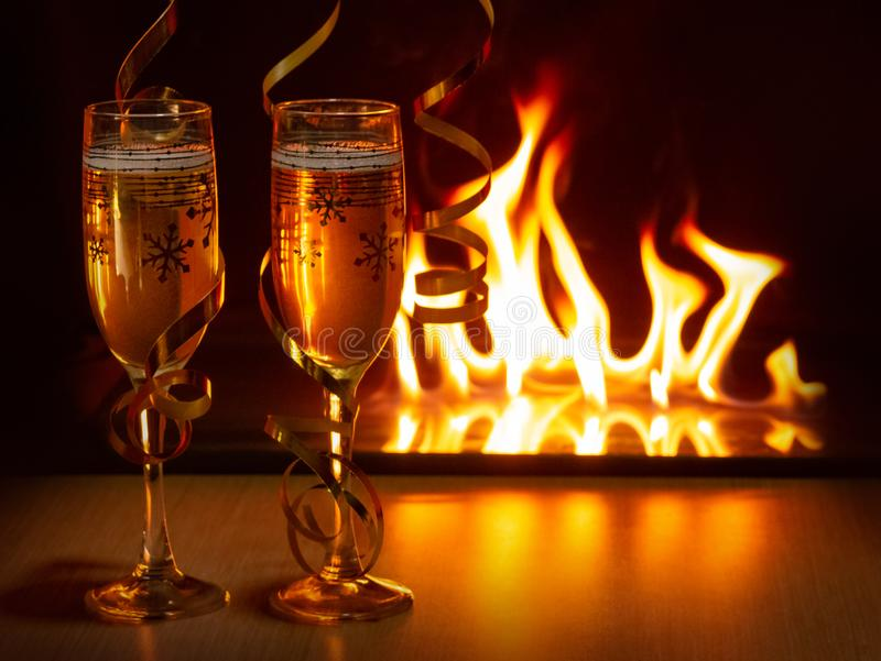 Two glasses of sparkling champagne with golden ribbons against the bokeh background of bright flames creating a cozy royalty free stock images