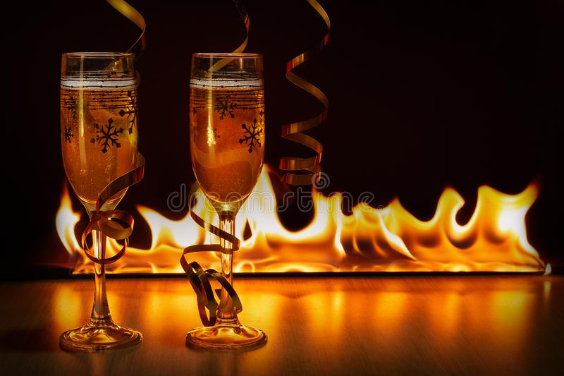 Two glasses of sparkling champagne with golden ribbons against the bokeh background of bright flames creating a cozy stock images