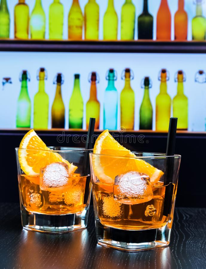 Two glasses of spritz aperitif aperol cocktail with orange slices and ice cubes on bar table, disco atmosphere background. Lounge bar concept stock photos