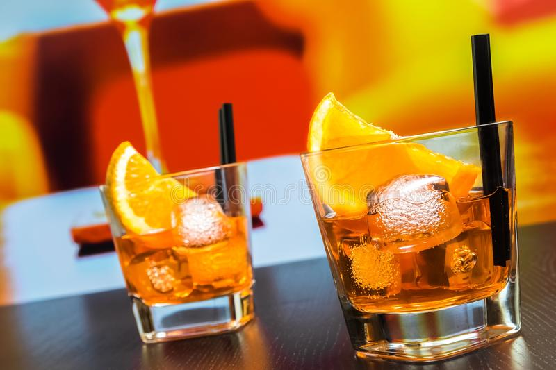 Two glasses of spritz aperitif aperol cocktail with orange slices and ice cubes on bar table, disco atmosphere background. Lounge bar concept royalty free stock photography