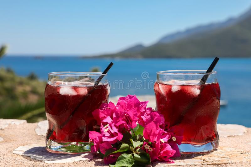 Two glasses of summer red cocktail with ice and a sprig of Bougainvillea flowers between on the seascape background. Summer sea vacation concept. Horizontal stock photography