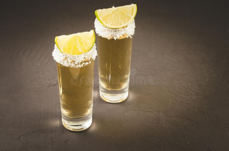 two glasses of tequila and pieces of lime /two glasses of tequila and pieces of lime on a dark stone background. Selective focus royalty free stock images