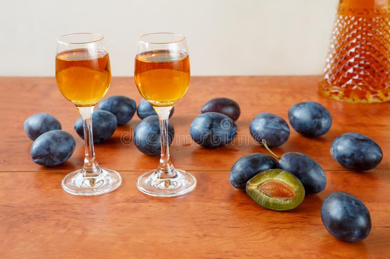 Two glasses of traditional bulgarian home made fruit brandy called slivova rakia or slivovica, half sliced and whole plums on a stock photos